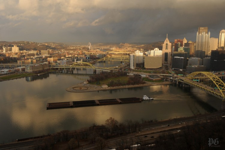 The sun peeks through the clouds as a coal barges heads up the Ohio River. Rebecca Droke/Post-Gazette