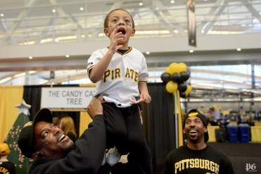 Weston White Jr., right, laughs as his father, Weston White Sr., left, holds White Jr.'s son Miayre White, 3, as he calls out to center fielder Andrew McCutchen and the rest of the Pittsburgh Pirates as they answer questions onstage during PirateFest. Michael Henninger/Post-Gazette