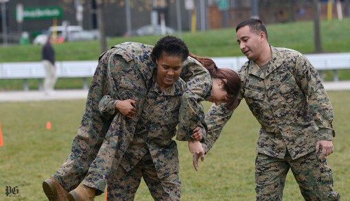 During the administration of the U.S. Marines' combat fitness test Sgt. Kemmala Kelsey lifts civilian volunteer Lisa Thomas and carries her down a marked path on the grass. (Larry Roberts/Post-Gazette)