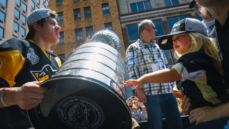 Evgeni Malkin and family members held the cup as it moved along Grant Street. (Steve Mellon/Post-Gazette)