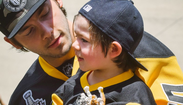 Kris Letang has a moment with his son Alexander. (Gracey Evans/Post-Gazette)