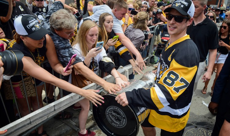 We loved this gesture -- Sidney Crosby brought the cup to fans standing along the boulevard. (Steve Mellon/Post-Gazette)