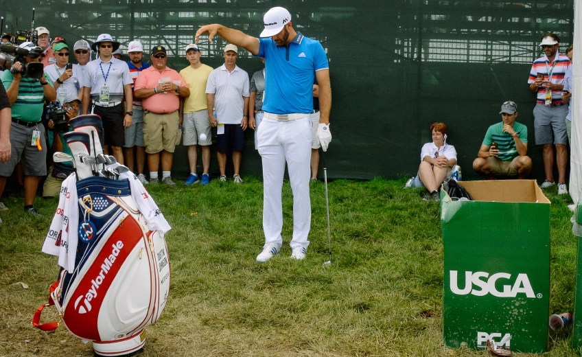 Dustin Johnson takes a drop after his ball hit someone's head and landed in a lemonade stand on the second hole during the third round. (Matt Freed/Post-Gazette)