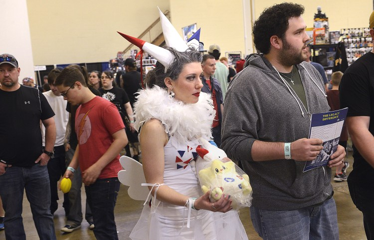 Larry Roberts/Post-Gazette    20160417   steel city con A2 layout Hope Swain (cq), from Bellevue,center, walks with her husband Eric Auth (right) through the Monroeville Convention Center dressed as Togekiss, from Pokemon, April 17, 2016