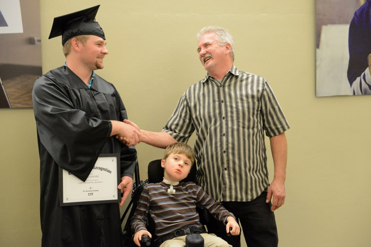 Shane Sanner, left, of Mt. Pleasant, shakes hands with his father Bob after taking photos with him and his brother Daniel, 7, at an ITT Technical Institute graduation ceremony at Pittsburgh Technical Colleges in Oakdale Wednesday, October 12, 2016. In September ITT abruptedly closed amid a federal inquiry. PTC stepped forward to host a graduation ceremony-- which eight students attended, providing caps and gowns for graduates.