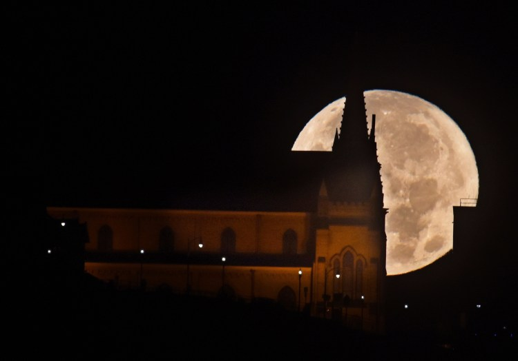 The supermoon moves behind Saint Mary of the Mount on Mount Washington Monday morning Nov. 14, 2016. The supermoon is also known as the Beaver Moon. (Darrell Sapp/Post-Gazette)