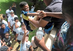 Pitt quarterback Kenny Pickett, bottom, and his teammates, help Jeremy Franklin, 8, of Highland Park to climb the obstacle wall drill at the Mel Blount Youth Leadership Initiative on Wednesday, July 26, 2017 in Claysville, Pa. The Pitt football teamÕs 2017 newcomers hosted a fitness and football clinic for kids at the camp. (Lake Fong/Post-Gazette)