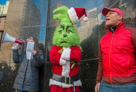 "Abby Cartus, left, a graduate student at the University of Pittsburgh and Douglas Ward, a United Steel worker, chant slogans outside Senator Pat Toomey's office while the ""Grinch"" listens on Wednesday, December 06, 2017 Downtown. Members of the USW Graduate Student Organizing Committee and their fellow University of Pittsburgh students delivered letters to Senator Pat Toomey, urging him to keep anti-education provisions passed by the House of Representatives out of the final version of the tax bill. (Lake Fong/Post-Gazette)"