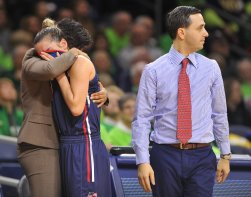 Robert Morris University's Anna Niki Stamolamprou gets a hug from assistant coach Kim Dweck after leaving the game late in the fourth quarter of their first round game in the NCAA Women's basketball tournament Friday, March 17, 2017 at Purcell Pavilion in Notre Dame. Head coach Charlie Buscaglia keeps tabs on the game on right. (Pam Panchak/Post-Gazette)