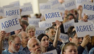 """People in the audience at the Sen. Bob Casey town hall held in Alumni Hall at the University of Pittsburgh hold up their """"agree"""" cards after the senator made the statement that the country needs to """"elect good candidates"""" on Sunday, Apr. 9, 2017. On the back of the card is the word """"disagree"""" for those with differing opinions. (Larry Roberts/Post-Gazette)"""