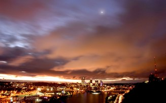 The Pittsburgh skyline highlights the low layer of clouds as the crescent Moon peers through the gap on Monday, October 16, 2017 in Pittsburgh. (Darrell Sapp/Post-Gazette)