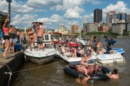 """Stacey Wehner, 30, of Ben Avon, raises her arm as she rides an inflatable bull in the Allegheny River while partying with her friends on Sunday, July 2, 2017 along the North Shore. The """"Sunday Funday Slip and Slide"""" party, thrown by Pittsburgh Boat Life for the fourth year now, brought out a series of DJs and a 100-foot slippery tarp for people to slide down the adjacent hill on. (Stephanie Strasburg/Post-Gazette)"""