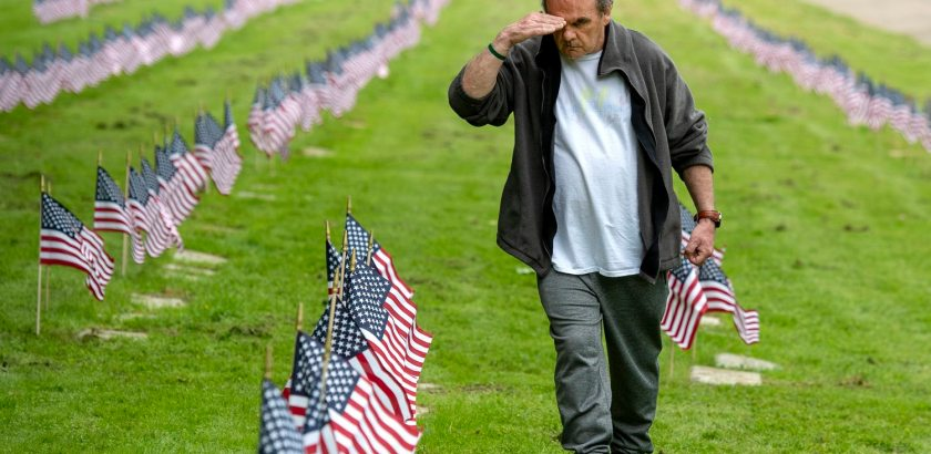 Former Army Sgt. Patrick Mcallister, 72, of Wilkinsburg, salutes after placing flags on the graves of military veterans with Pittsburgh Mercy Intellectual Disabilities Services on Wednesday, May 22, 2018, at Allegheny Cemetery in Lawrenceville. (Steph Chambers/Post-Gazette)