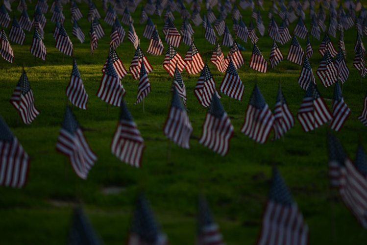 Evening light illuminates flags place on the gravesites of veterans in advance of Memorial Day, on Wednesday, May 23, 2018, at the Allegheny Cemetery in Lawrenceville. (Rebecca Droke/Post-Gazette)