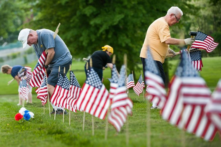 """American Slovenian Catholic Union members Mike Lewis, left, 71, of Fox Chapel, and Mike Helwich, right, 69, of Ohio Township, volunteer to place American flags at the graves of Veterans on Monday, May 21, 2018, in preparation for Memorial Day at Allegheny Cemetery in Lawrenceville. """"We put them at the person's heart,"""" said Bloomfielder Marlene Scholze, 58, of placing the flags on the right side of the graves above the hearts of the vets buried below. """"They fought for our country, that's where their heart is."""" Scholze helps organize the volunteer effort to place flags on some 15,000 veterans graves.(Stephanie Strasburg/Post-Gazette)"""