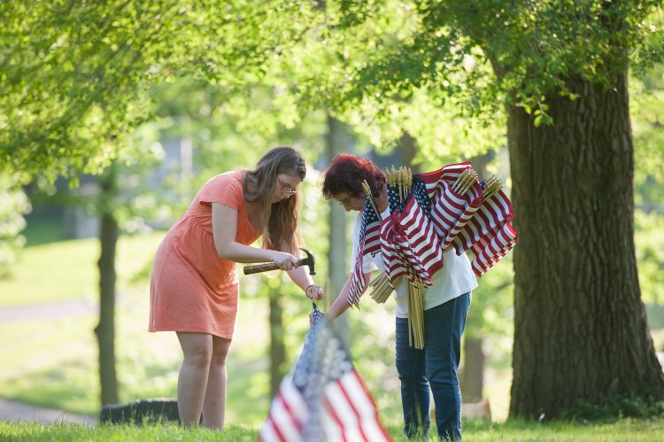 Theresa Rocky, left, and Vanessa Romano place flags on the gravesite of veterans in advance of Memorial Day, on Wednesday, May 23, 2018, at the Allegheny Cemetery in Lawrenceville. (Rebecca Droke/Post-Gazette)