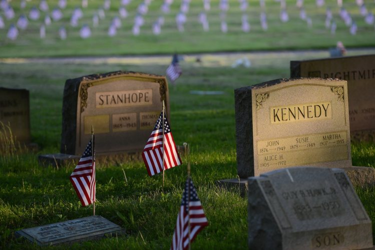 Evening light illuminates flags place on the gravesites of veterans in advance of Memorial Day, on Wednesday, May 23, 2018, at the Allegheny Cemetery in Lawrenceville. (Rebecca Droke/Post-Gazette