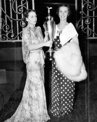 "Gwen Wakeling, a 20th Century-Fox designer, awards a silver trophy to Leaver, who was crowned ""Miss Model America of 1936."" (ACME photo)"