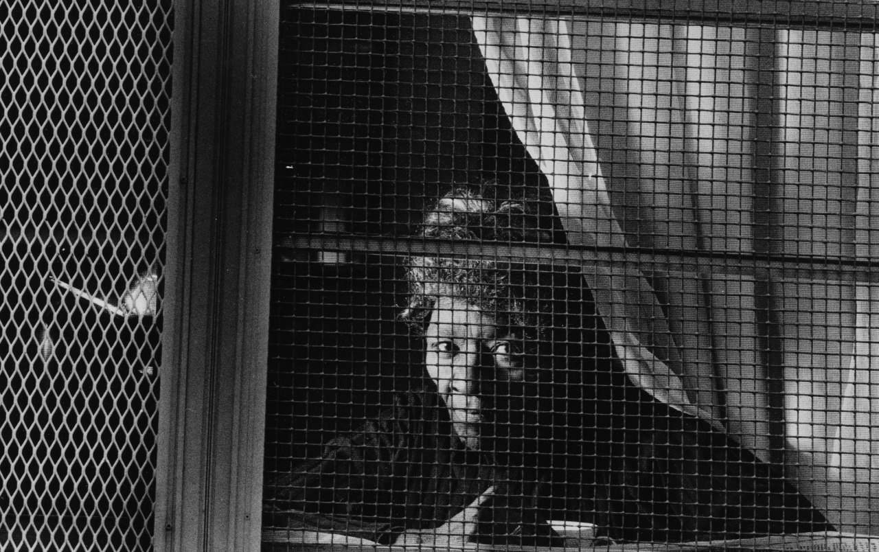Feb. 1, 1990: Ardmo Fuller, president of the Metropolitan Tenants Organization, looks out the window of her Bedford Dwellings apartment. (Peter Diana/Post-Gazette)
