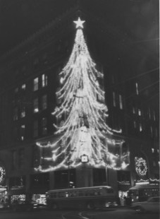 A trolley passes the Christmas tree that adorned a Downtown Pittsburgh deparmtent store in 1960 at Penn Avenue and Stanwix Street.