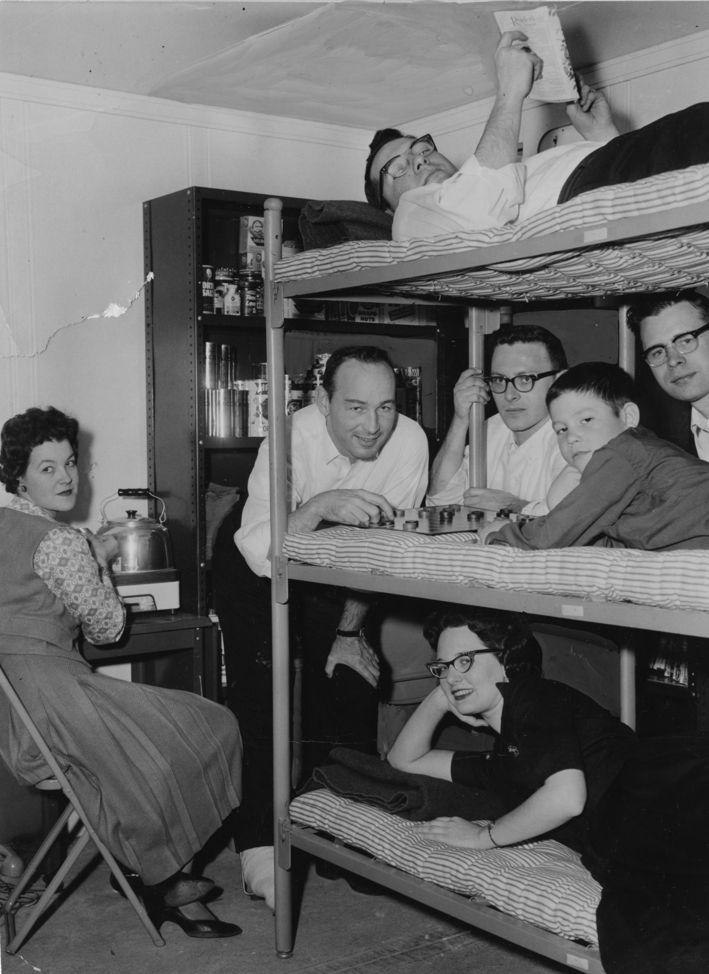 """March 18, 1960: The seven people who spent last weekend in a simulated fallout shelter at American Institute of Research, 410 Amberson Avenue, Shadyside. On the top bunk, Robert Smith, reading. Nancy Newton is at the """"kitchen"""" stove at left. Second bunk: Frank McKenna, Gil Dannels, Tommy McKenna, 8, and James Altman. In lower bunk is Sara Bryson. (Bill Levis/Pittsburgh Sun-Telegraph)"""