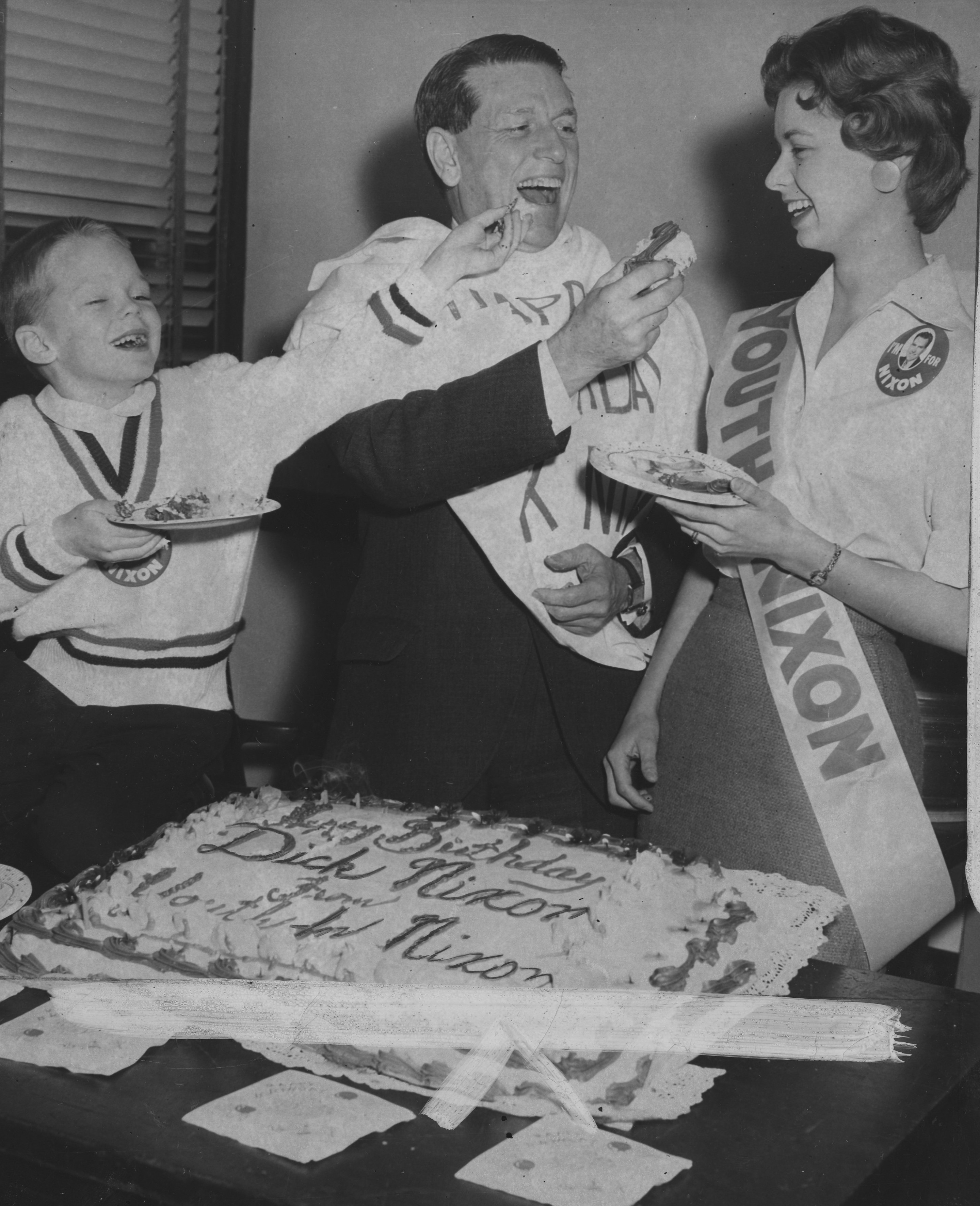In 1960, Youth for Nixon celebrated Vice President Richard M. Nixon's 47th birthday with cake in the organization's Frick Building office. From left to right are Robbie Dunbar, Rep. James G. Fulton, head of Allegheny County's Nixon backers and Carolyn Mutz.