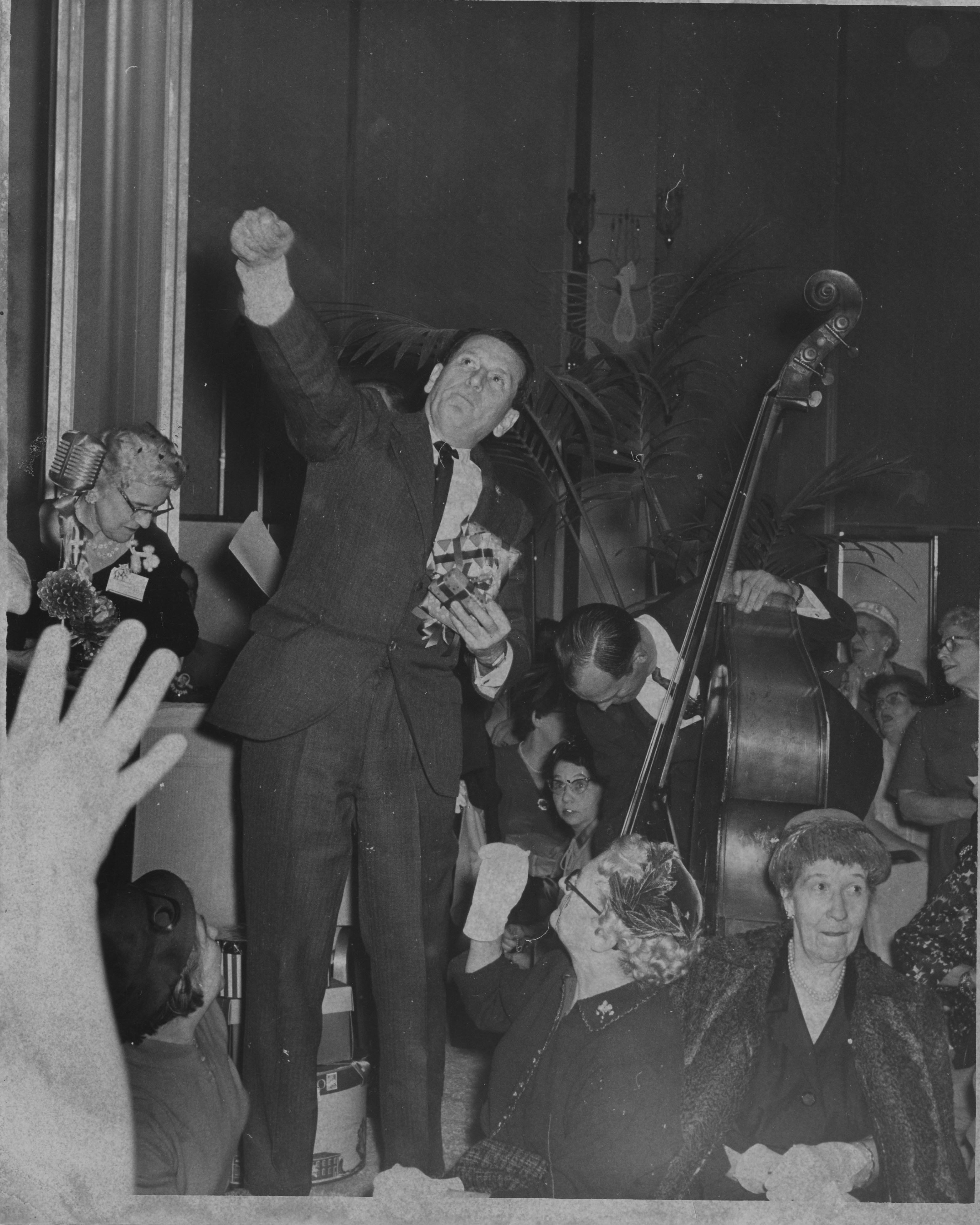 U.S. Congressman James G. Fulton hurls gifts to a crowd of guests at a political shindig for Richard Nixon in 1959.