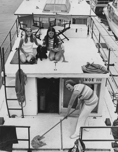 This 1970 image shows Mrs. Tyler swabbing the deck of a houseboat called Tippecanoe III while her daughters, L'Vonne and Lynda sunbathe.