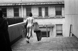 Holding his clothing, the streaker heads for a set of steps. (Morris Berman/Post-Gazette)