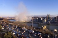 The dust cloud eminating from the imploded Three Rivers Stadium rolls over the city as spectators leave Pittsburgh's Mount Washington section on Sunday morning, Feb. 11, 2001. (Keith Srakocic/Associated Press)
