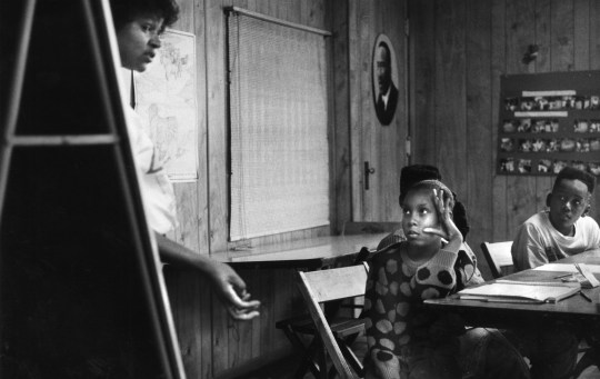 Chareese Matthews, 10, center, and Gwetto Martinez, 12, got a lesson in black history from Marsha Jones of Concerned Parents of Wilkinsburg, a volunteer tutor filling in during the 1991 strike. Five students attended the class in the basement of Mount Calvary Baptist Church. (Tom Ondrey/The Pittsburgh Press)