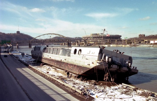 When waters receded at the Allegheny Wharf, the 200-foot Pittsburgh Wind Symphony barge ended up on a parking lot with cars under it (Martha Rial/Post-Gazette, Jan.21,1996)