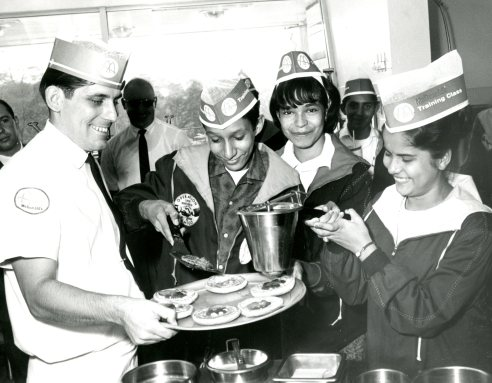 Getting an assist in kitchen of McDonald's and a hamburger for Amigos, 1965.