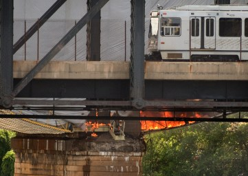 A light rail vehicle pauses the watch the tarp fire on Friday, Sept. 2, 2016. (Steve Mellon/Post-Gazette)
