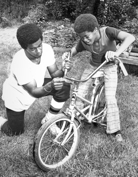 Helping a neighbor with a bicycle problem. (The Pittsburgh Press)