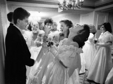 Susan Beard, 18, center, pretends to slap escort Ron Rosati, 20, shortly before entering the ball and being named 1988 Cinderella. With them are left Dana Herrmann, and Priscilla Beard. (Bill Wade/The Pittsburgh Press)