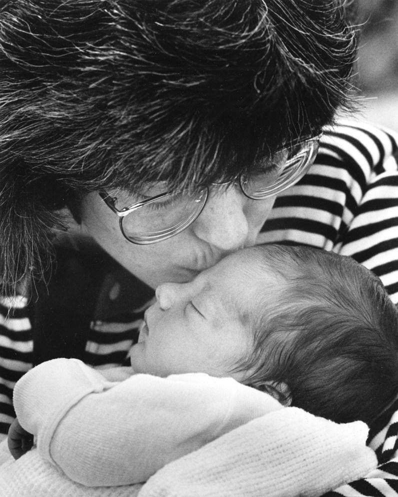 Ellen Kline plants a kiss on her newborn son's forehead. (Darrell Sapp/Post-Gazette)