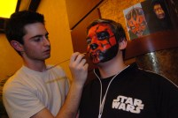 """George Tropster, left, a student at the Art Institute majoring in Industrial Design/Special Effects Makeup, paints Mike Cartier's, 13, from Carmichaels, face as """"Darth Maul"""" at a Star Wars Premiere Party at Loews at the Waterfront in advance of the first showing of """"Star Wars: Episode III: Revenge of the Sith"""" at 12:01 a.m. Thursday, May 19, 2005. (Alyssa Cwanger/Post-Gazette)"""