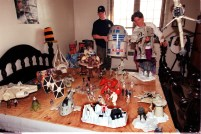 "Mt. Lebanon's Paco Carioli, 20, and his mother Cyndie Carioli exhibit their ""Stars Wars"" Collection, from R2D2 which Paco is holding to the AT-AT that Cyndie is holding, and the B-Wing Fighter hanging from the ceiling, on March 28, 1997. (Robert Pavuchak/Post-Gazette)"