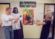 """Matt Rogers, left, and Valerie Micher joust with toy lightsabers they have in their """"Star Wars"""" display at their offices at ServiceWare, Inc. in Oakmont, Pa., Friday, May 7, 1999. (AP Photo/Keith Srakocic)"""