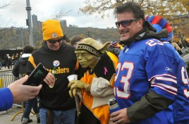 "Brian Rasbach, left, of Atlanta, Ga., and Jason Cataldo, right, from Durham, N.C., poses for photos with a Steelers-clad statue of Yoda from ""Star Wars"" in the parking lot outside Heinz Field, Nov. 10, 2013. (Larry Roberts/Post-Gazette)"