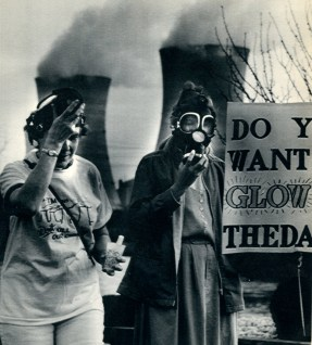 Two protestors wear gas masks while attending a 1989 anti-Three Mile Island rally on the 10th anniversary of the accident. In the background, steam rises from the undamaged, restarted Unit 1 facility. (Associated Press)