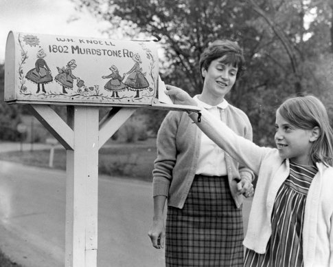 Amy Knoell takes a letter from the mailbox her mother, Anna Knoell, decorated with Pennsylvania Dutch figures. Photo published Oct. 20, 1968. (Pittsburgh Press)