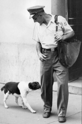 Mailman Charles Busha is investigated by Spotty. Photo published Aug. 9, 1959. (Pittsburgh Press)
