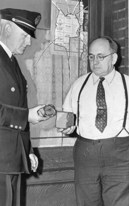 Lt. Bert Keller inspects evidence with E.J. Conrad, manager of the Conrad Cafe at 4214 Main St. in Bloomfield. Keller is holding a large bomb fragment while Conrad shows him the brick thrown through the window behind them. Photo published Nov. 9, 1946. (Pittsburgh Press)