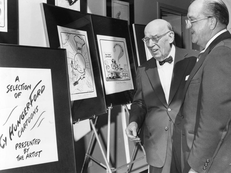 Hungerford and Anthony Martin, head of Carnegie Library of Pittsburgh, look at a display of cartoons at the Downtown branch of the library. Photo published Oct. 14, 1975.