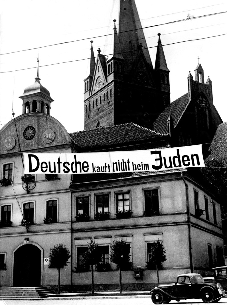 """Hundreds of posters asking Germans to boycott Jewish shops hung throughout Germany, like this one on a street in Greifenberg, Pomerania on Aug. 8, 1935. This sign reads, """"Germans don't buy in Jewish shops."""" (Associated Press)"""