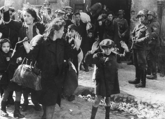 A group of Jews, including a small boy, is escorted from the Warsaw Ghetto by German soldiers on April 19, 1943. (Associated Press)
