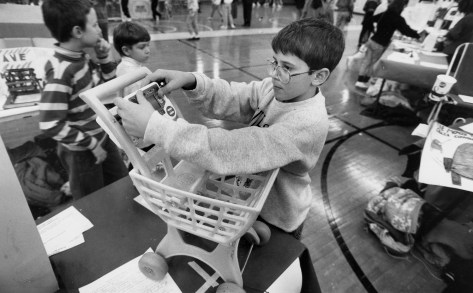 Ben Mauti, a fifth grader at E.L. Shepard, adjusts his invention, a shopping cart with a video game attached to it, Dec. 12, 1991. He said that when he goes shopping with his mother he often sees screaming, bored kids, so he invented this to help time go faster. (Pittsburgh Press)