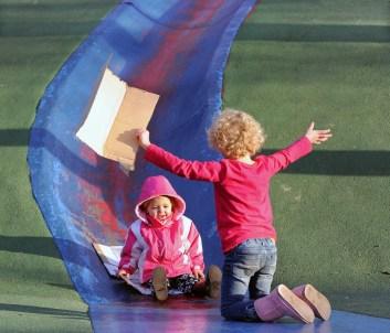 Millaney Wiegand, 2, and her sister, Kalliyan, 5, of Penn Hills slide the blue slide, Dec. 26, 2011. (John Heller/Post-Gazette)
